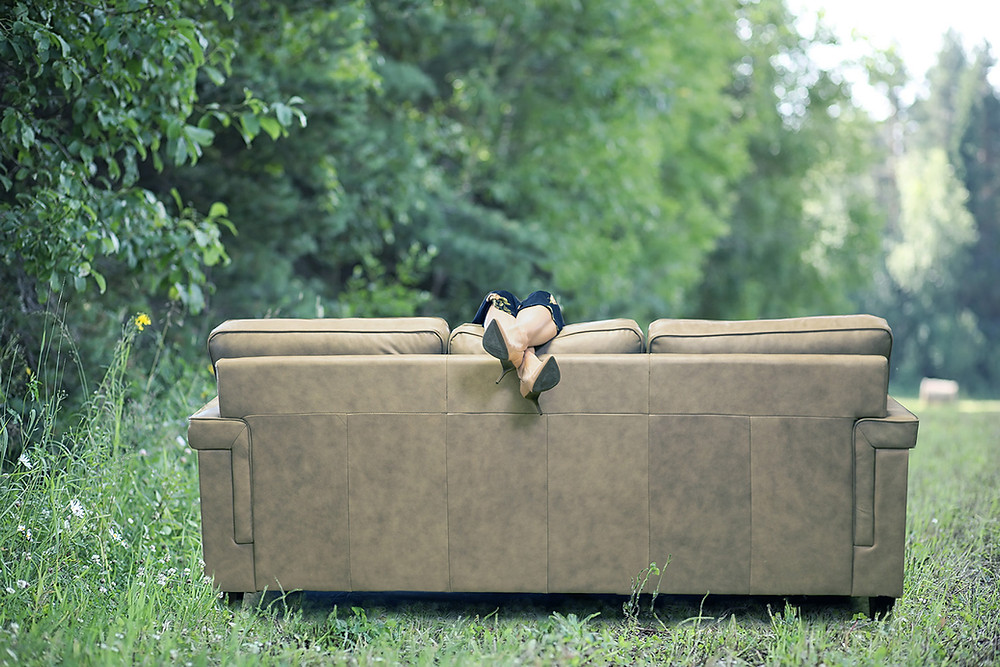 Legs donning black high heels dangle over the back of a leather couch in a field by a treeline