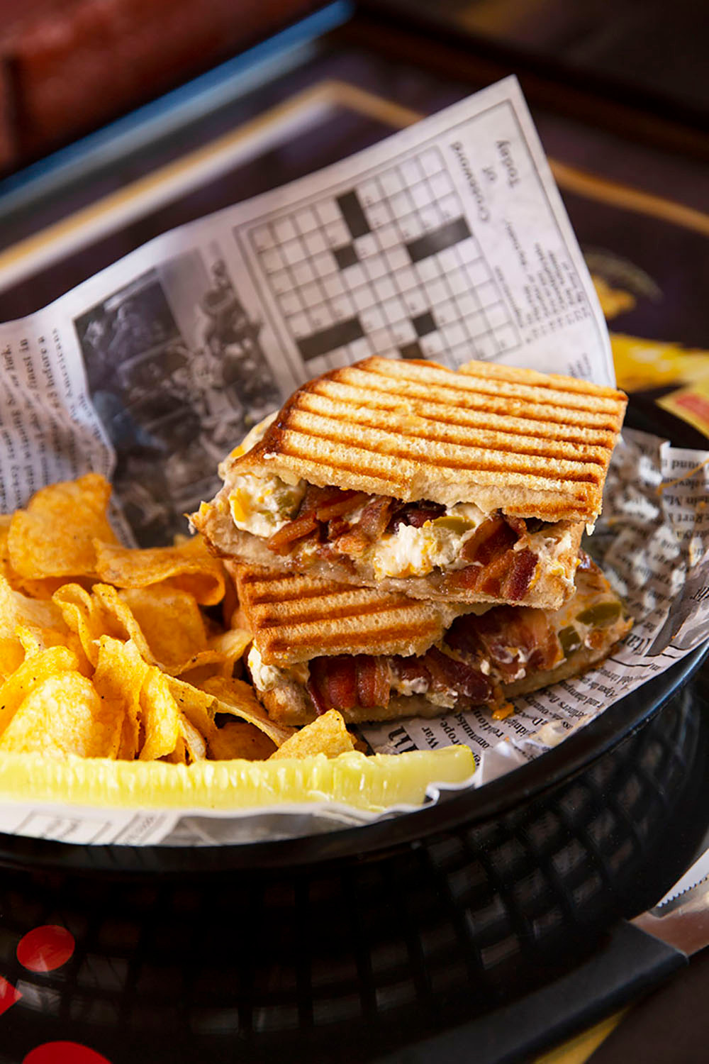 Cheesy sandwich with jalapenos and bacon cut in half with bar-b-que chips on a plate