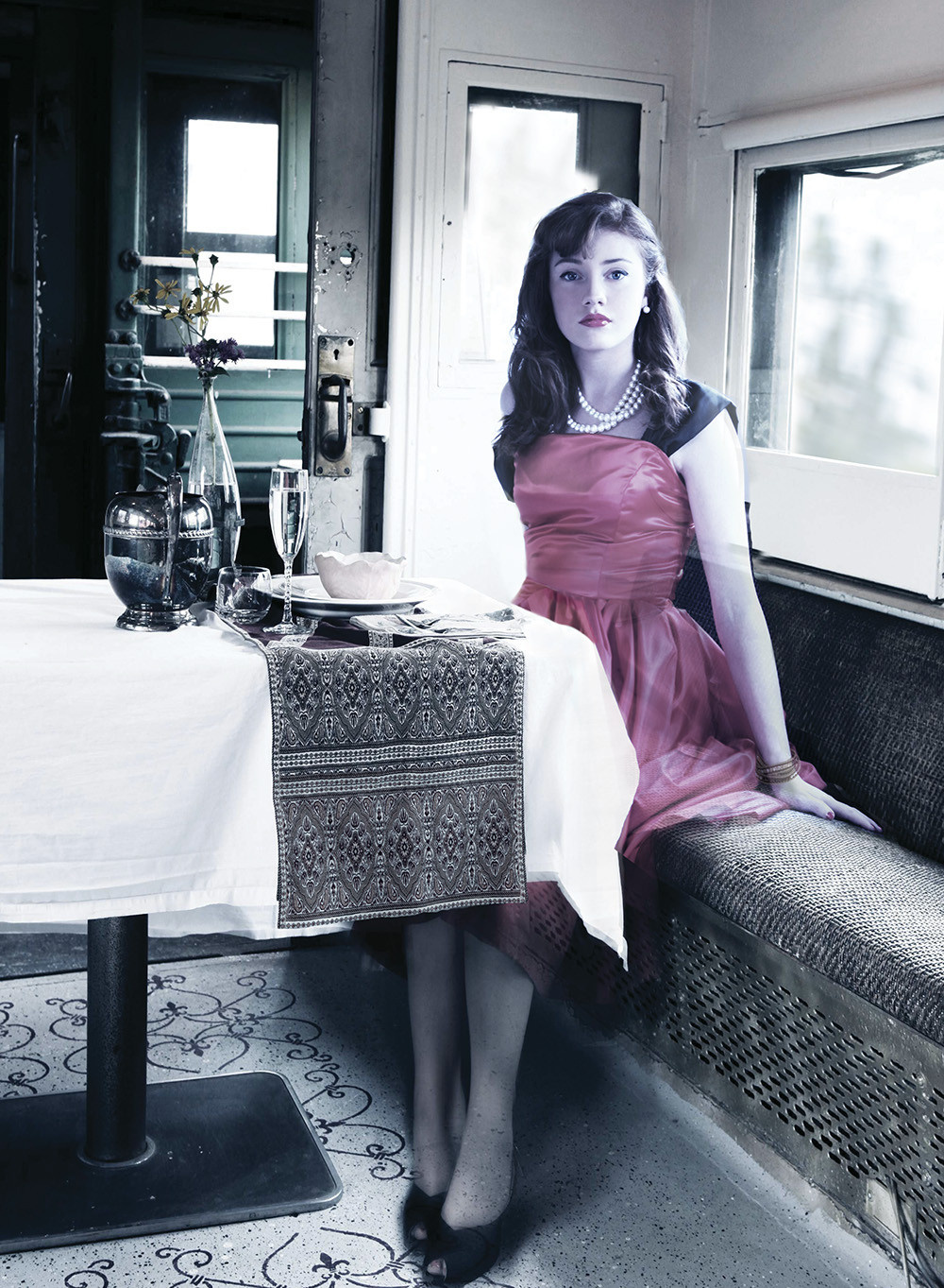 young beautiful woman in 1940's clothing/style in the dining car of an old train