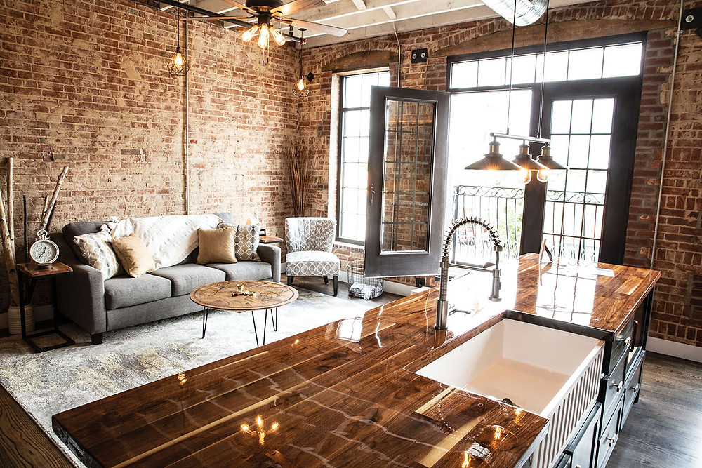 brick urban loft with full service kitchen and livingroom nicely decorated with double glass doors going to rod iron balcony
