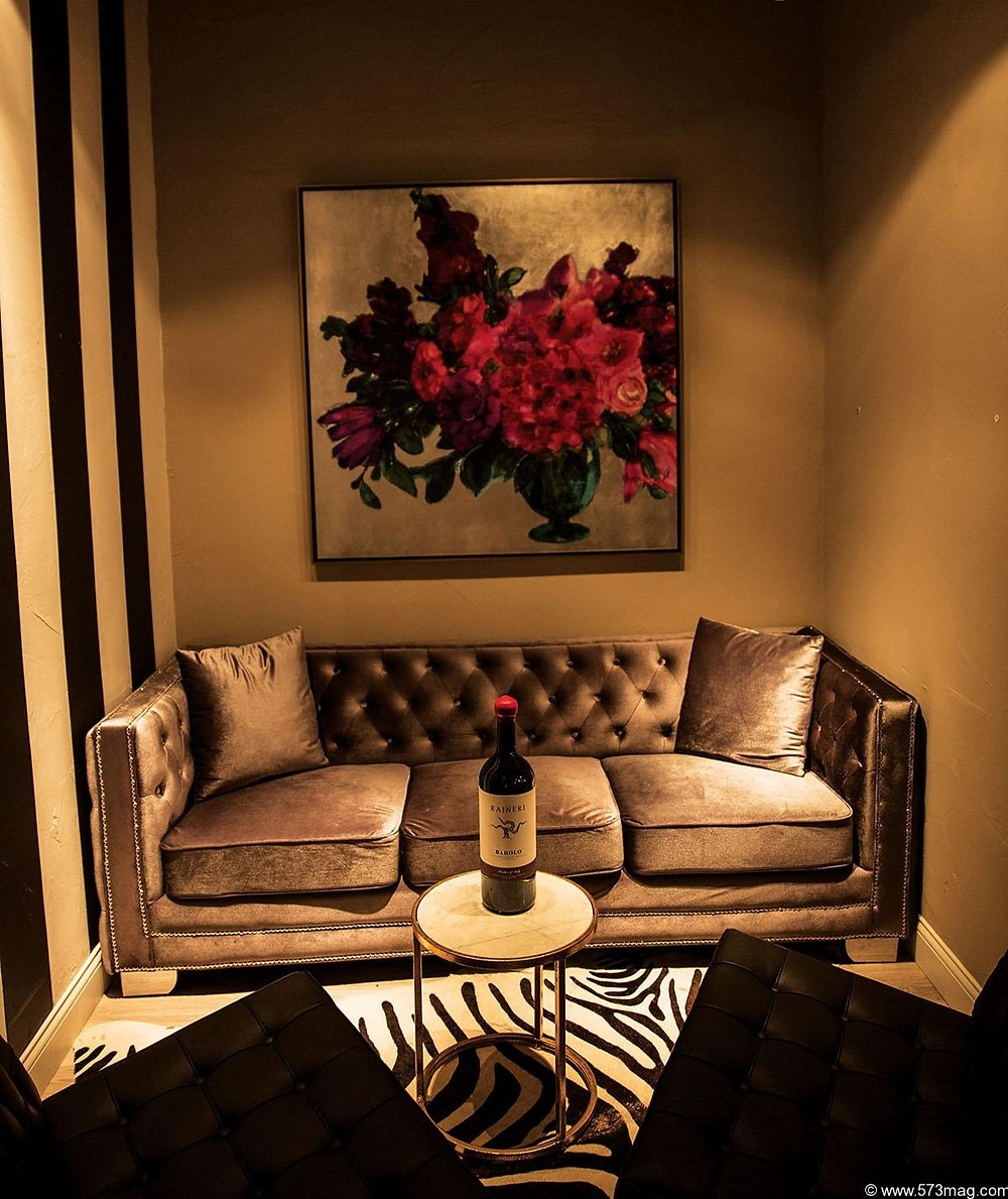 A stylish and comfy lounge with a vintage velvet couch displays a beautiful painting of a vase overflowing with large red flowers