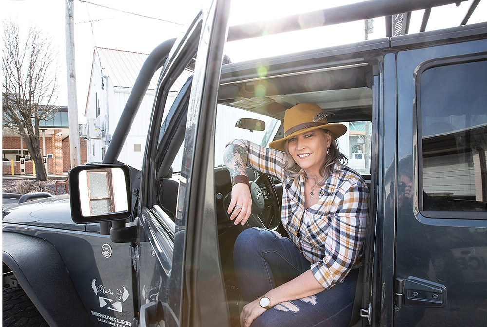 Beautiful woman with feathered fedora ripped jeans and flannel shirt rolled up to show tattoo sleeve on right arm sits in her jeep