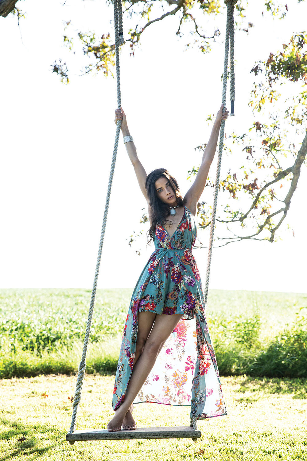 Mayada Jamila in a floral lady romper from A Simply Chic Boutique standing on the swing in the big oak tree photo op at The Barn at Lone Eagle Landing wedding venue