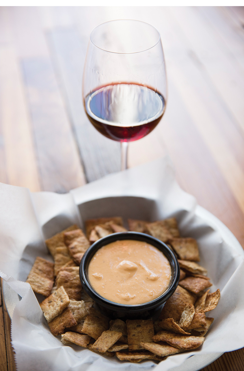 dish of gourmet crackers and dipping sauce with a glass of red wine