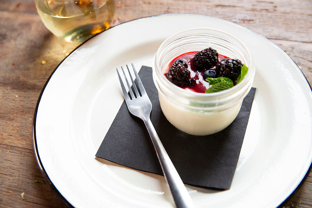 Dessert dish filled with Panna Cotta with raspberry coulis garnished with fresh berries and mint served with white wine