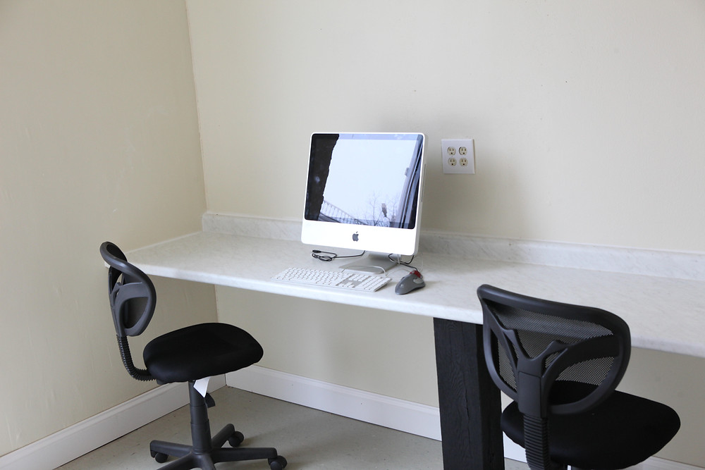 Vacant office with desk, chairs, and a computer