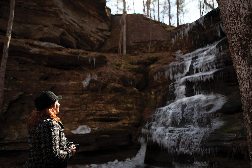 young woman smiles in awe at a frozen waterfall as the setting sun lights up her face