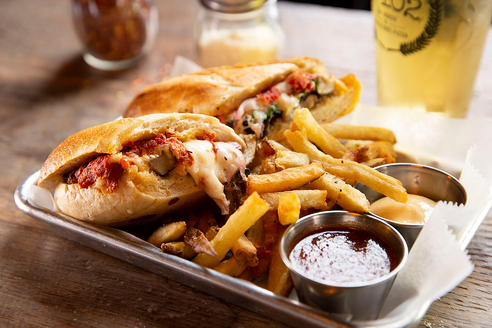 cheesy loaded vegetarian sandwich cut in half with a large helping of fries, 2 dipping sauces, and a draft beer