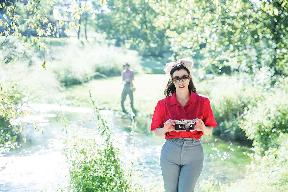 brunette woman in sunglasses with camera by river and fly fisherman casting from bank