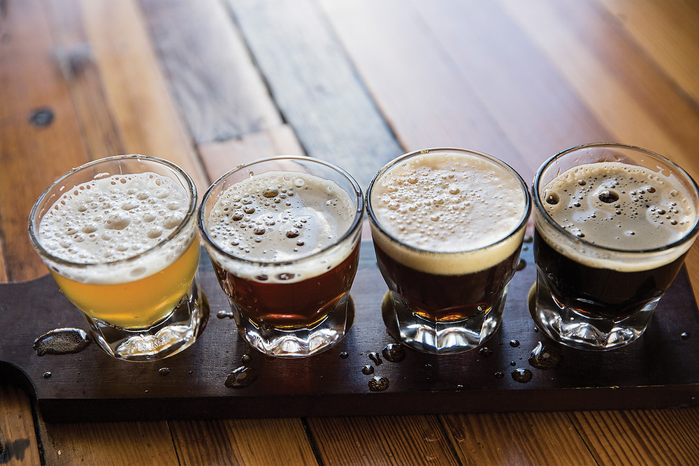 Sample platter with four glasses of different colored craft beers