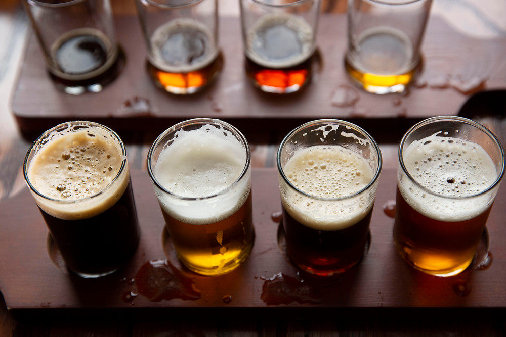 Four different beer samples of different colors and tones in four shot glasses await a taster at Minglewood Brewery