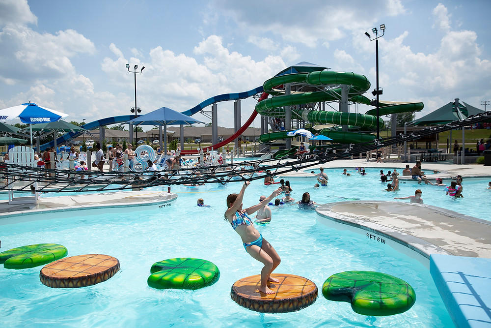At a large busy waterpark a young girl plays on floating foot pads while climbing across the pool with a large hanging net