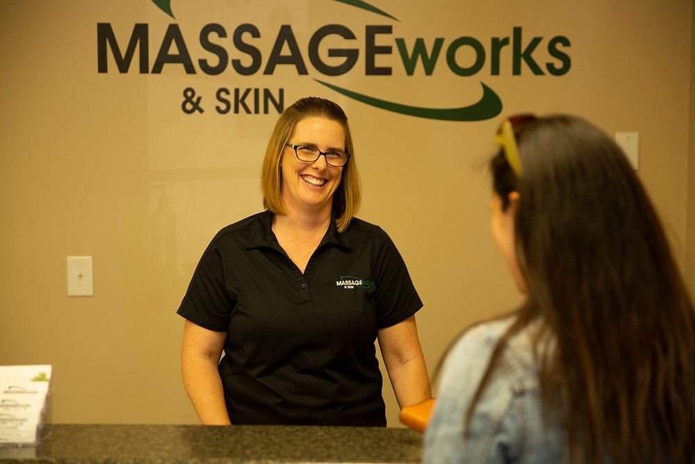 Woman with warm smile greets AJ at the front desk of Massage & Skin Works