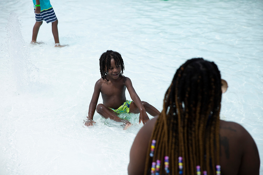 A small child with long dreadlocks splashes in a wading pool by his mother with long beaded braids