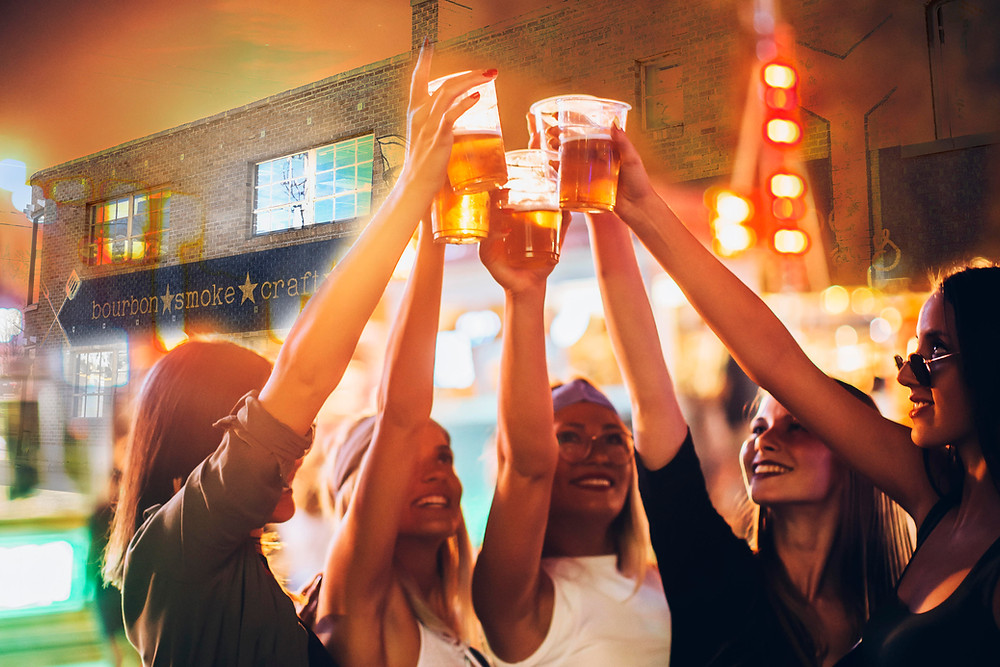 5 young attractive happy women at a street party with bright lights raise their glasses to toast