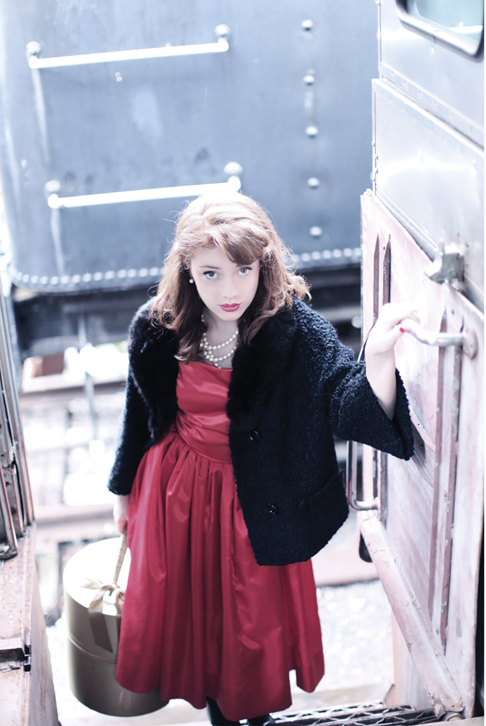 young woman with 1940's victory roll in a red dress and black fur coat boards an old train carrying a hat box
