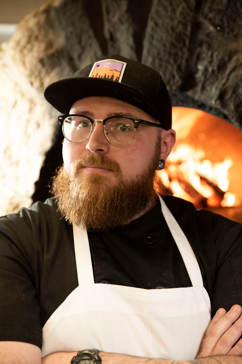 Man with beard and glasses stands cross armed and confident in front of his brick oven at The Old No. 102 Tap House