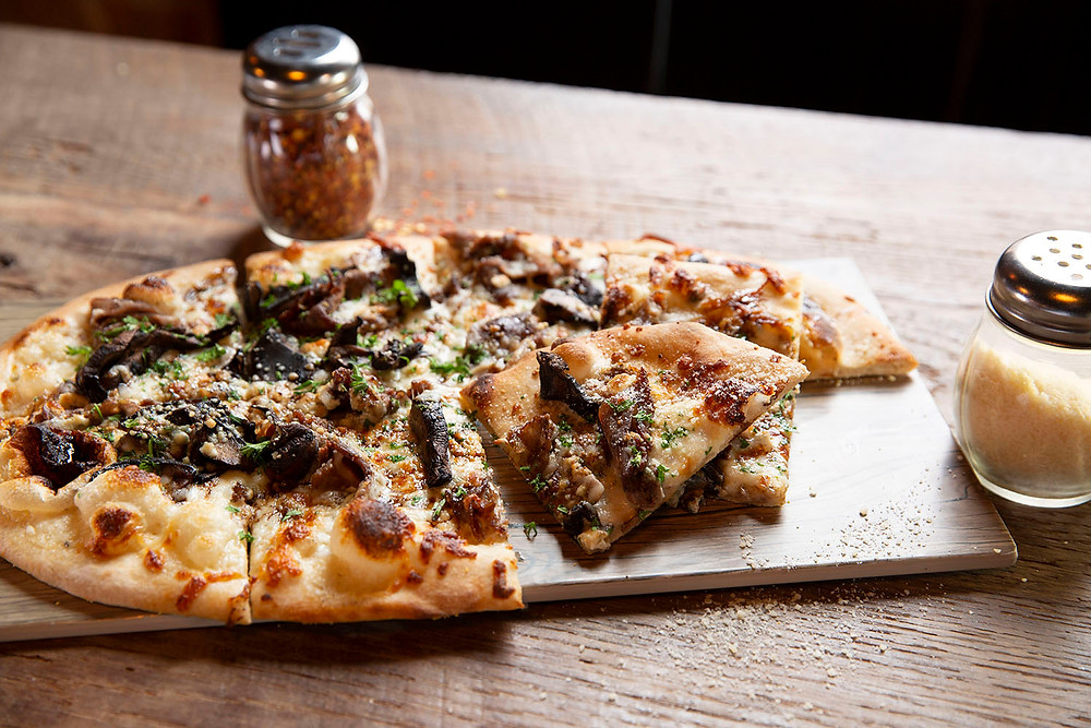 Large pizza with sirloin, mushrooms, cheese and an alfredo sauce on a table by parmesan and red pepper shakers
