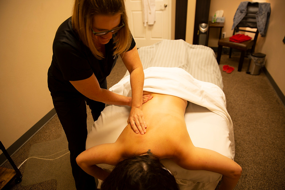 Woman laughs as she finishes the clients massage and tries to wake her