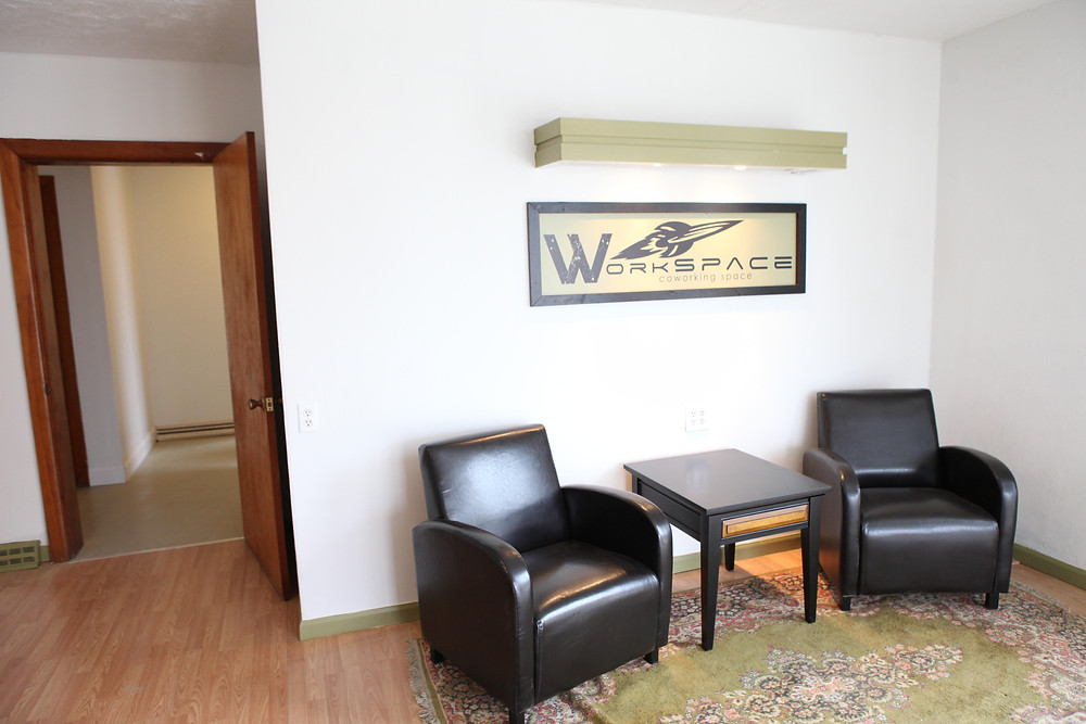 Lobby with leather chairs, table, large beautiful rug, and a sign with a flying saucer that says WorkSPACE