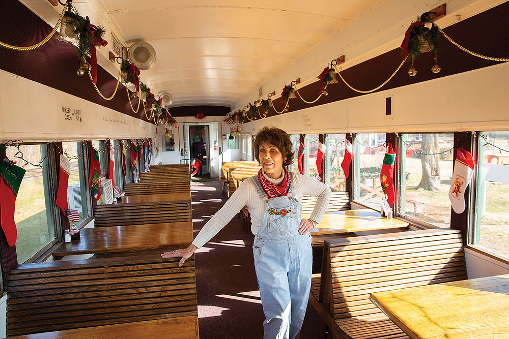 Elane Moonier shows off the inside of a dining car on the train decorated for Christmas