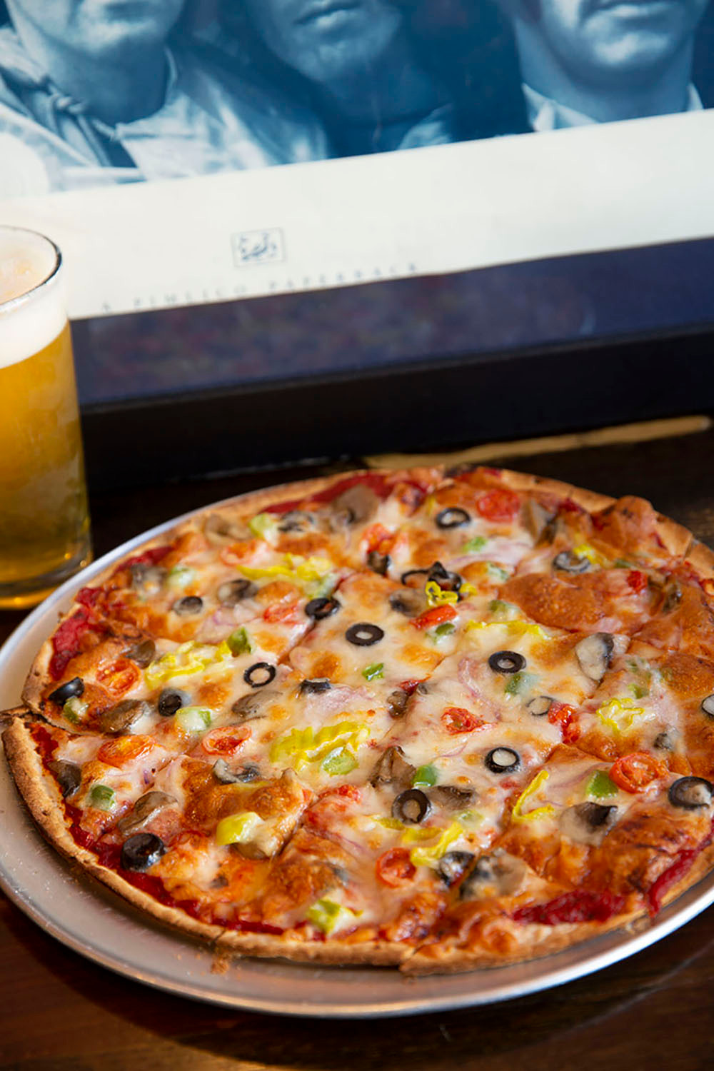 Large thin crust pizza loaded with olives peppers and other veggies with a glass of beer at The Brick Bistro & Brew