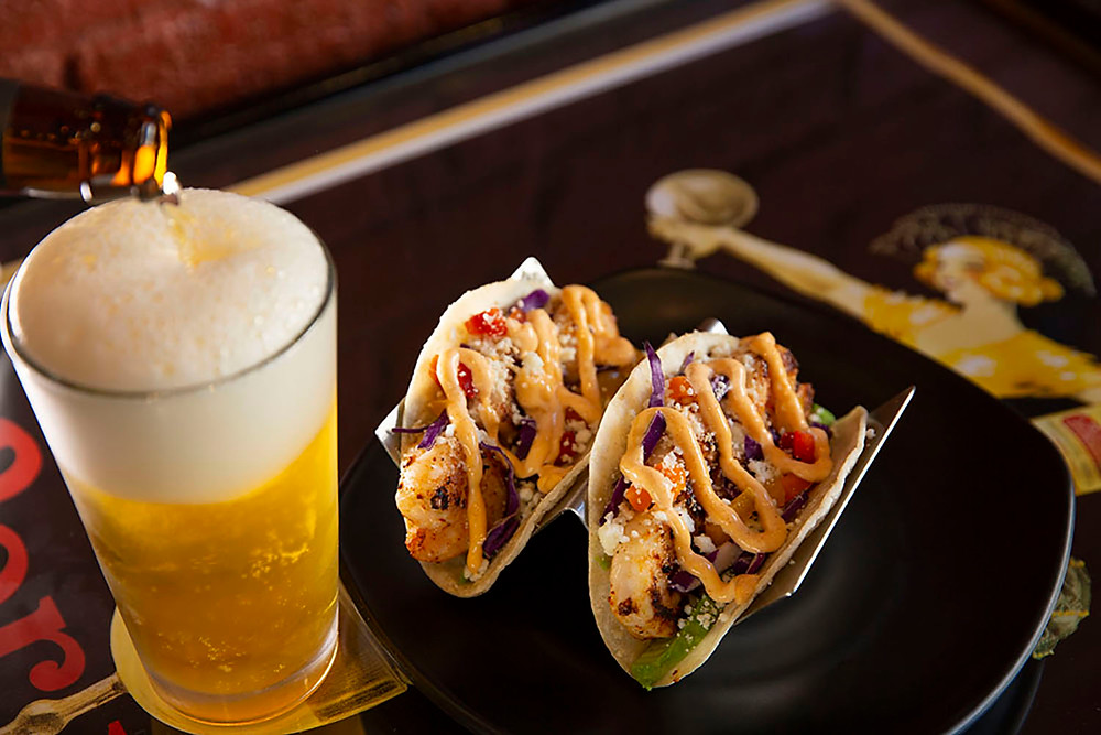 Two brightly colored shrimp street tacos on a plate with a tall glass of beer being poured