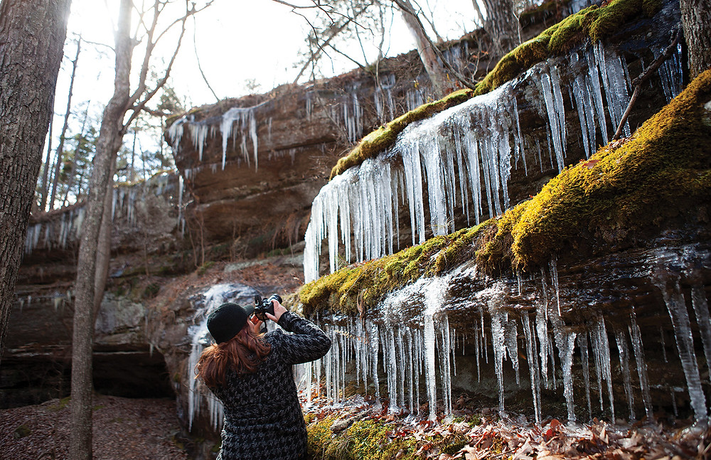 a young woman takes amzing photo of giant icicles hanging from moss covered banks of Hickory Canyon