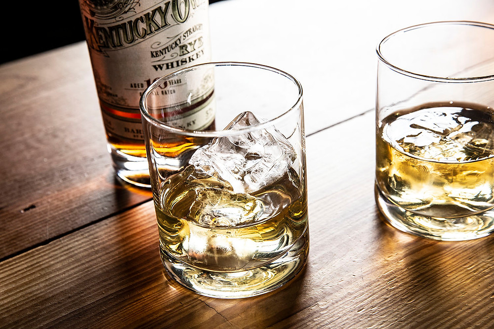 Bottle of Kentucky Rye Whiskey standing behind 2 glasses of bourbon on the rocks