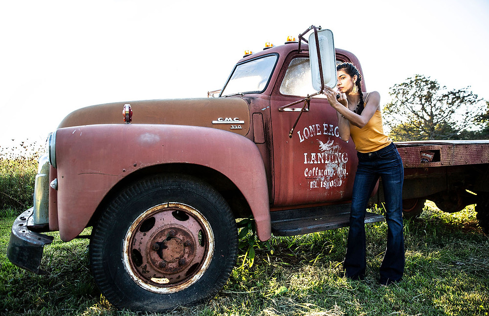 classic truck GMC 150 photo op at The Barn at Lone Eagle Landing wedding venue with Mayada Jamila in mustard tank and jeans from A Simply Chic Boutique