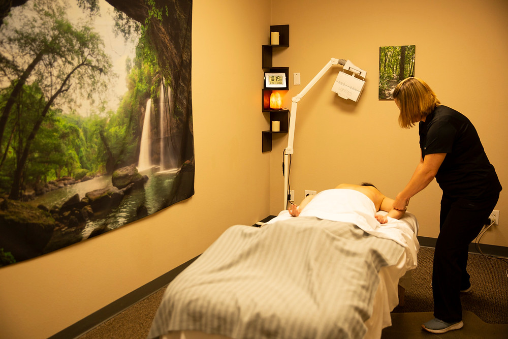 Woman massages client's arm in a large room with a serene picture of a natural forest and waterfall on the wall