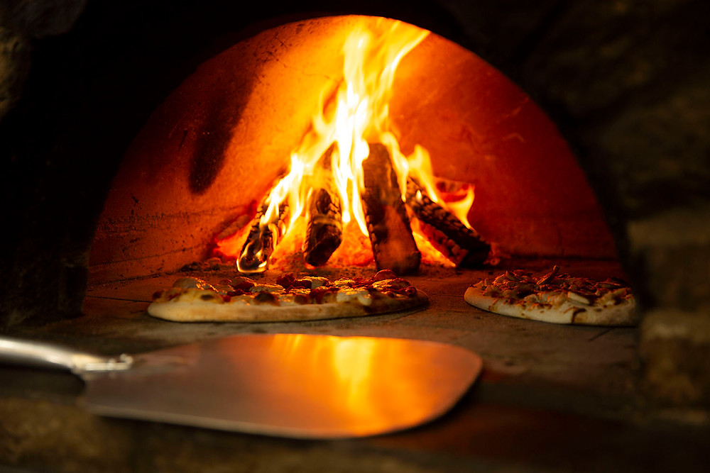 Fire bakes 2 pizzas and its reflection dances on a large metal spatula inside the brick oven at Old No. 102