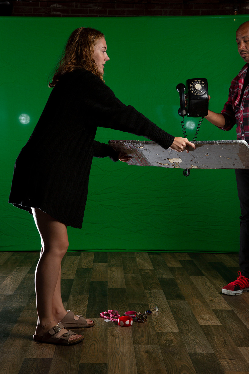 photography assistants hold rotary phone and bounce board in front of greenscreen at photo shoot at Mary Jane's