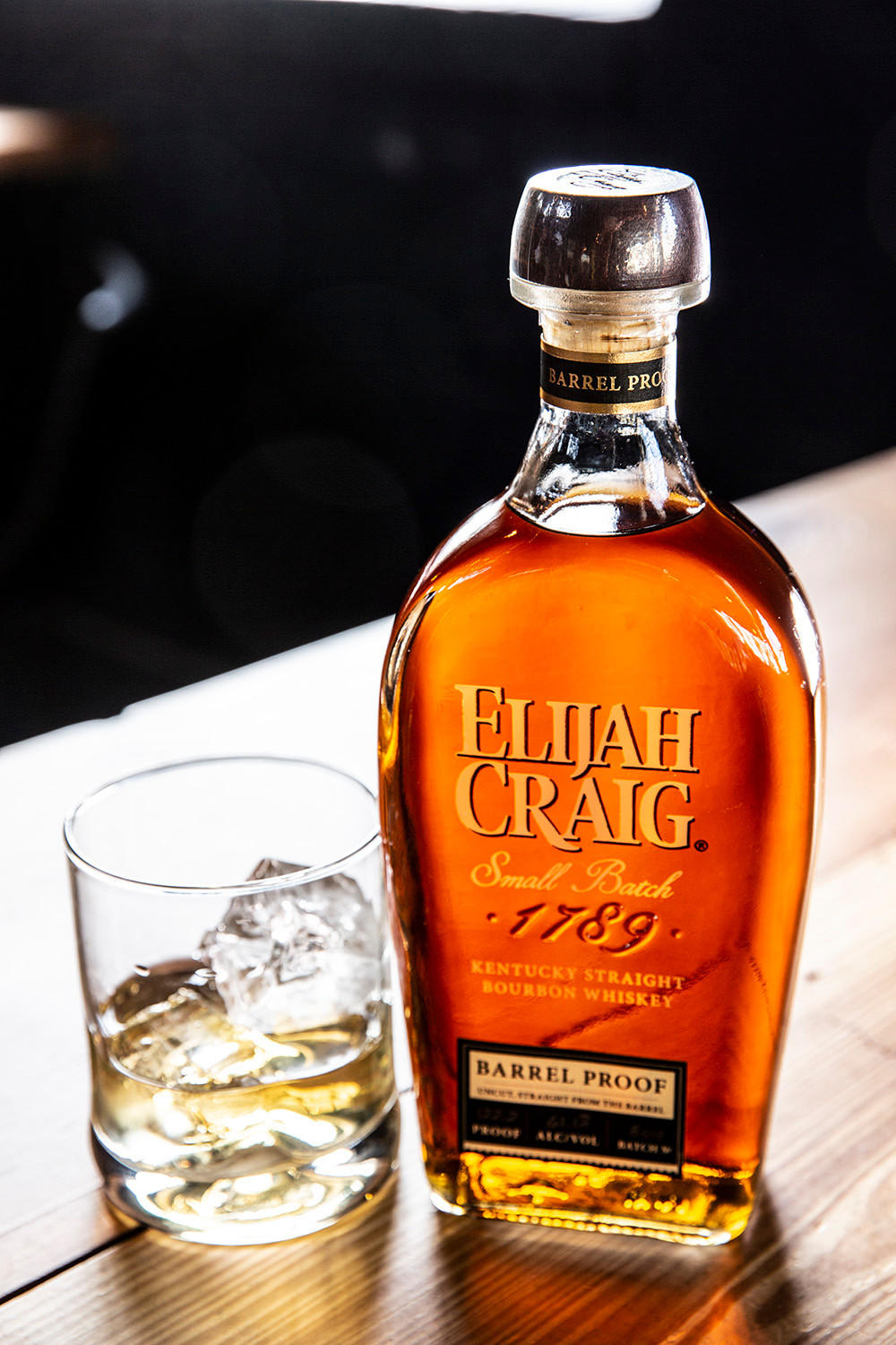 Bottle of Elijah Craig Bourbon next to a glass with bourbon and ice