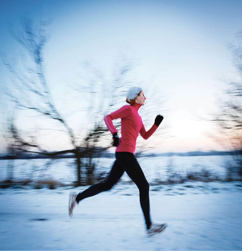 young woman jogs on a snow covered back road with the wind stinging her reddened nose and cheeks