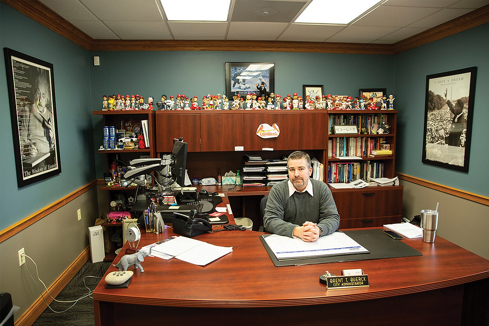 A man sits at a large wooden desk With a bookshelf behind him containing files, books, and a top shelf full of Cardinal bobble-head figurines