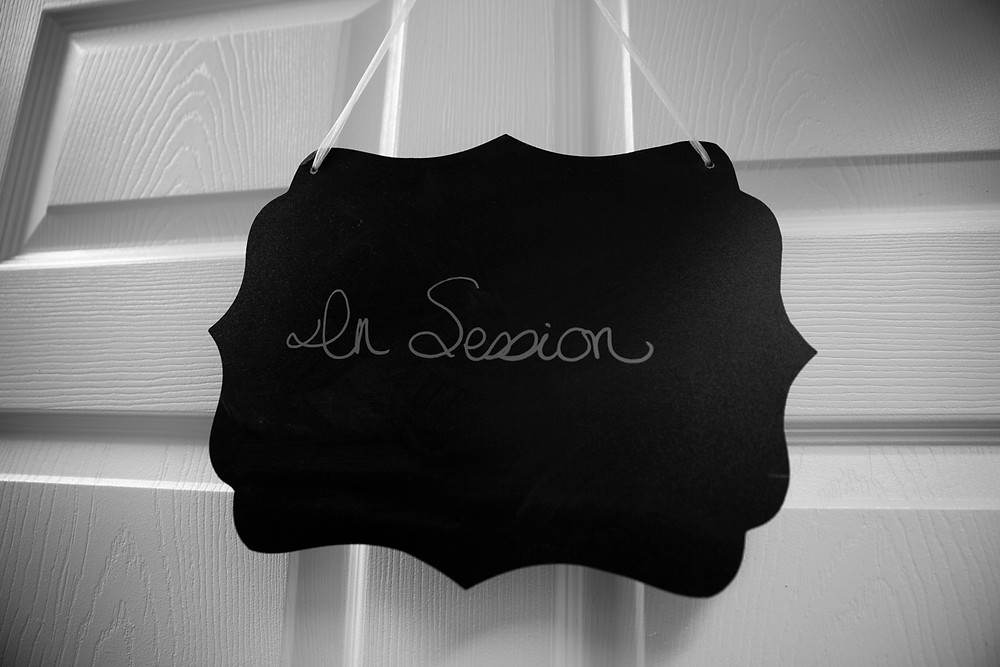 """A sign hanging on a closed door reads """"In Session"""""""