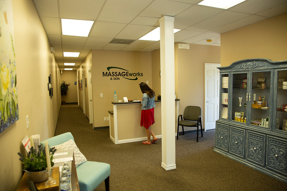 Woman in light and comfortable lobby signs in at Massage & Skin Works in Farmington