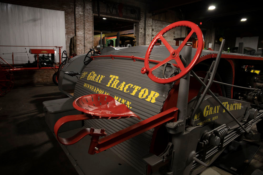 An antique Gray Tractor with bright red steering wheel and seat at the American Tractor Museum