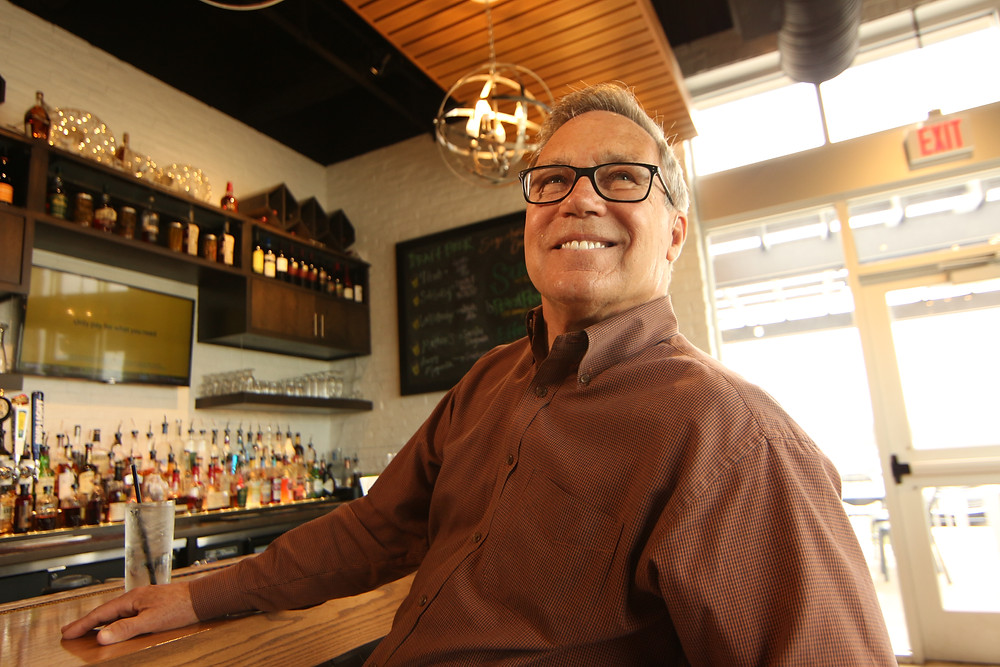 A man in glasses smiles broadly seated at a bar with a gin and tonic beneath a trendy modern spherical lighting fixture