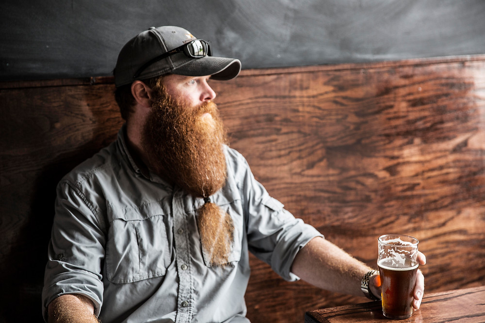 Man with a long red beard sits by a large window drinking a stout beer
