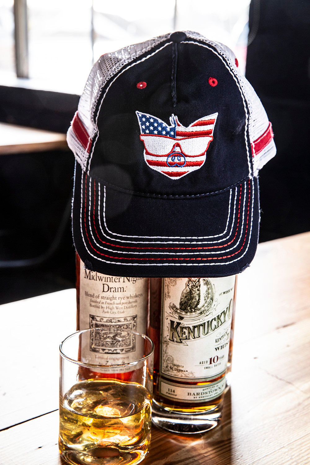 A baseball cap with an American flag colored pig on it sits atop 2 bottles of bourbon behind a glass of bourbon on the rocks