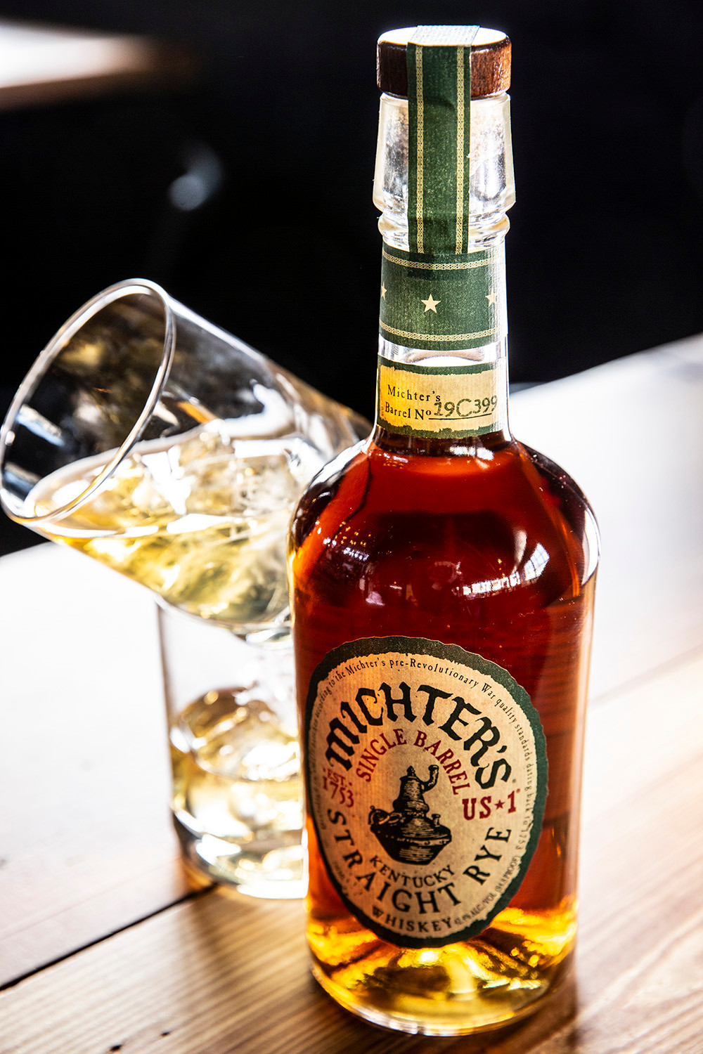 Bottle of Michters Rye Bourbon next to 2 bourbon on the rocks one balancing on top of the other