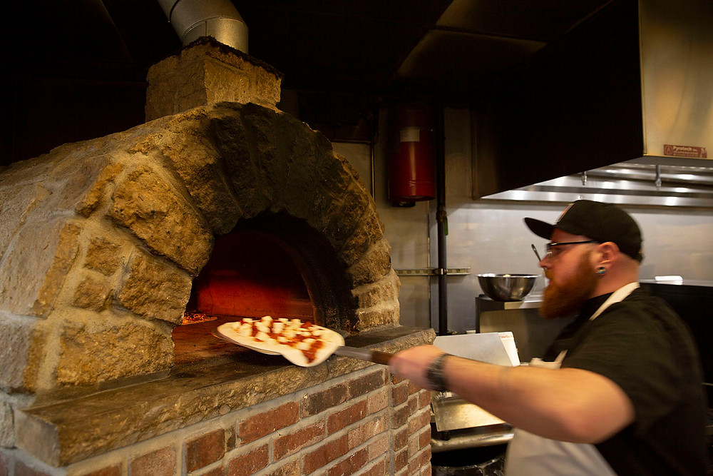 bearded man loads a pizza into a large brick oven at The Old No. 102 Tap House in Farmington