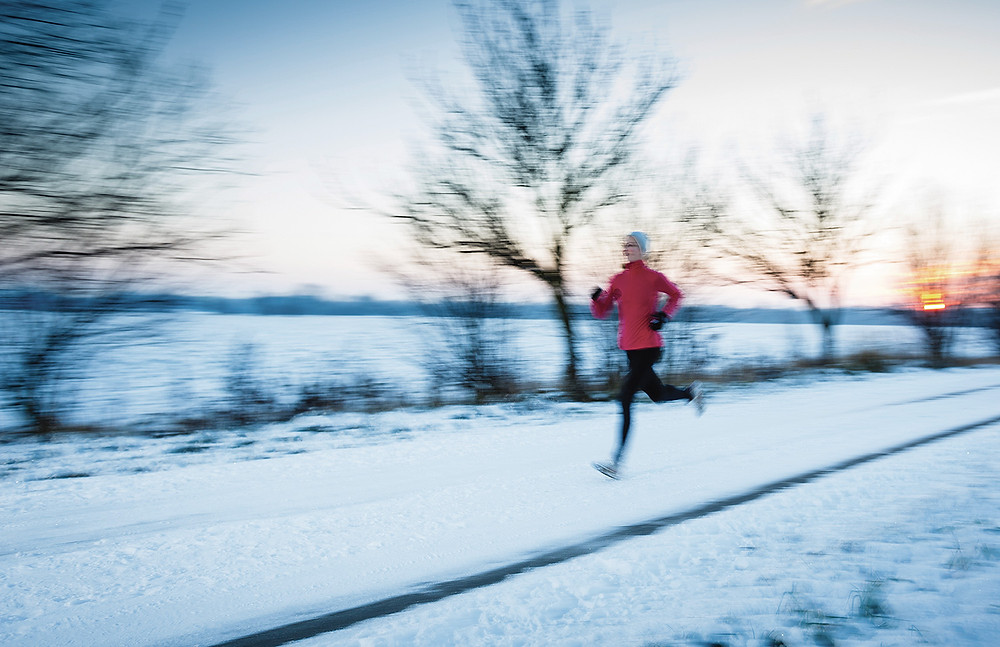 young woman running fast past a frozen lake in a winter wonder land at sunset