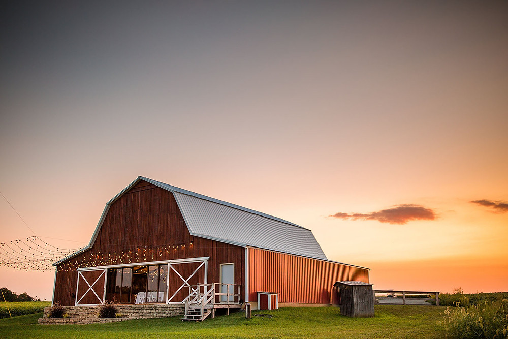 The Barn at Lone Eagle Landing wedding venue with outdoor dance floor and twinkle lights at sunset
