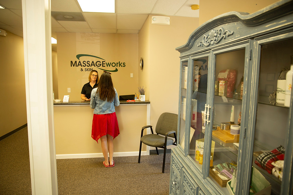A woman checks in to get a massage at the front desk next to a large antique china cabinet full of products at massage and skin works