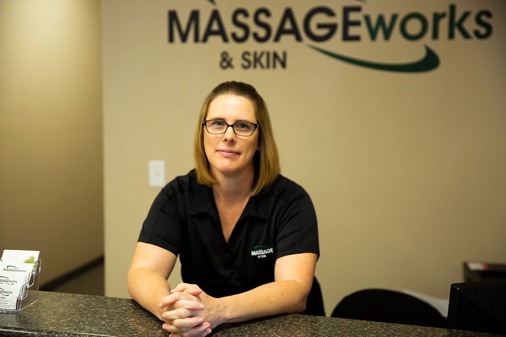 A woman sits smiling behind a desk, ready to help you at Massage & Skin Works