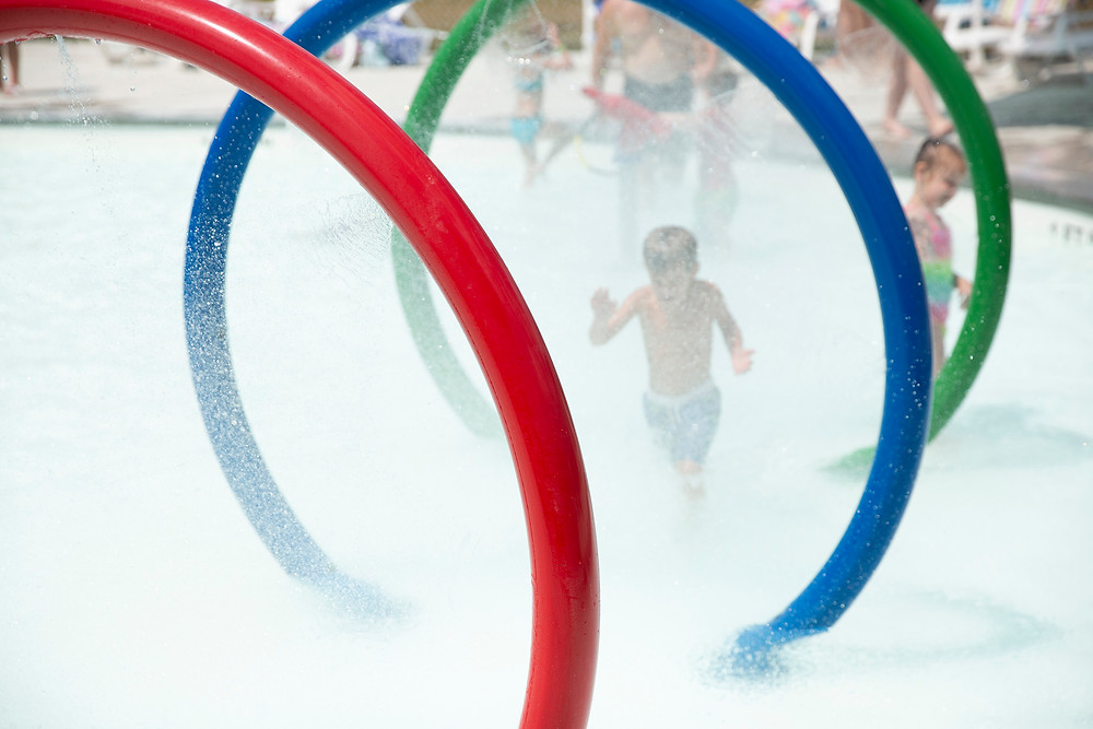 Children run through large colorful hoops as they're sprayed with sprinklers in the Kid Zone at River Rapids Water Park