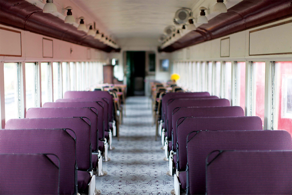 Long center aisle between 2 rows of seats in a passenger car on an old train